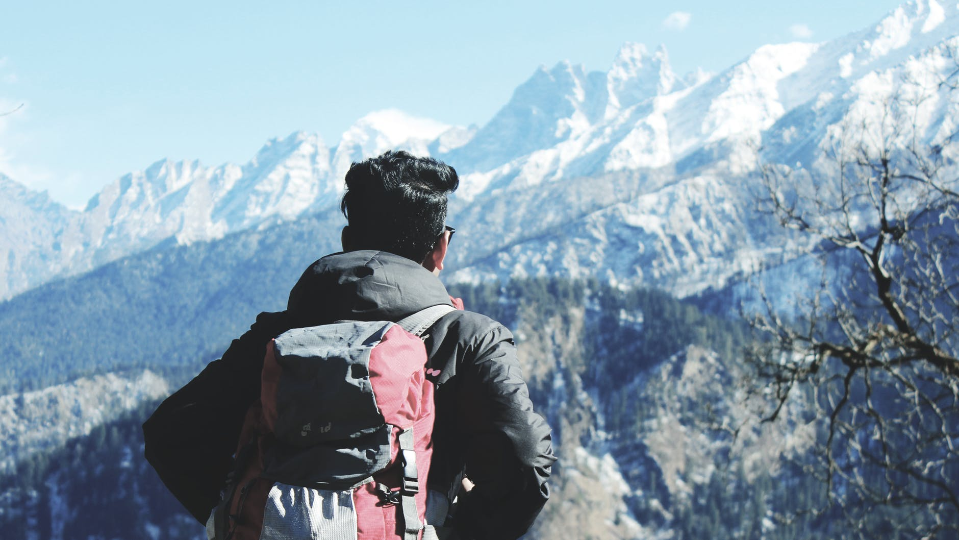 photography of man in black hooded jacket and red backpack facing snow covered mountain