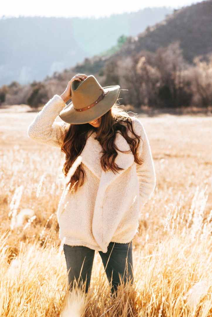 smiling woman in white winter jacket wearing brown cowboy hat surrounded of brown grass field
